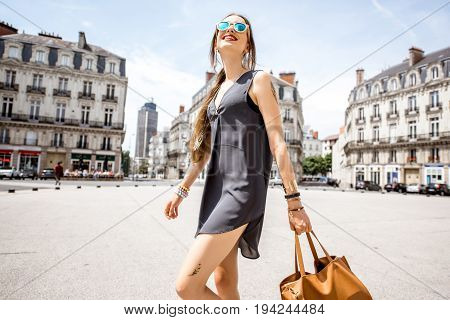 Young woman walking with bag on saint Pierre square with famous Brittany tower on the background in Nantes city in France