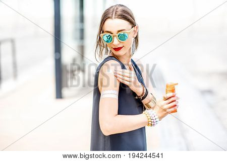 Young woman applying sunscreen lotion standing outdoors at the urban location during the sunny weather
