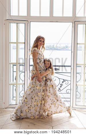mother and daughter in matching dresses standing at an open window on the sea background