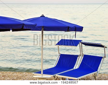two sunbeds on a stony beach with calm sea in background
