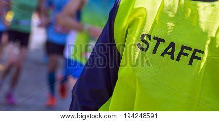 yellow bib staff service working during a marathon