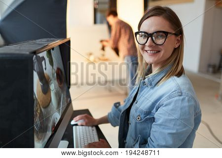 Young food-designer or blogger sitting in front of computer in studio