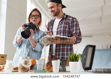 Young woman showing good shots in photocamera to colleague while shooting food