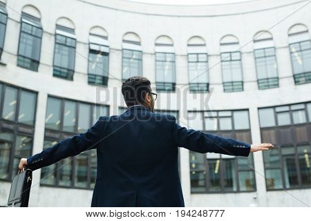 Successful businessman with briefcase standing in front of modern building with outstretched arms
