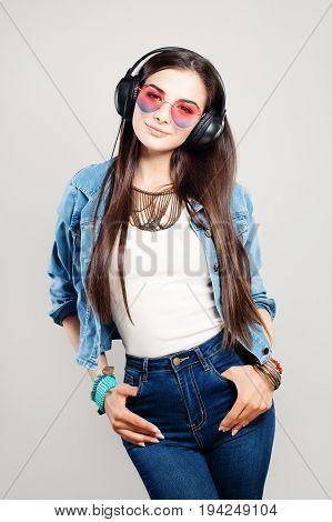 Happy Fashion Girl Enjoying the Music. Young Beautiful Woman with Earphones and Denim Jacket