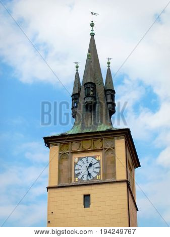 The Old Town water tower with its neo-Gothic roof and clock dated 1880 rises into a partly cloudy sky in Prague, Czech Republic.