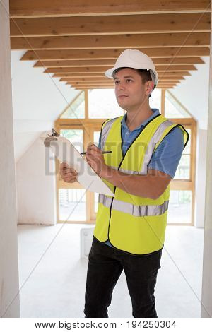 Building Inspector Looking At Interior Of New Property