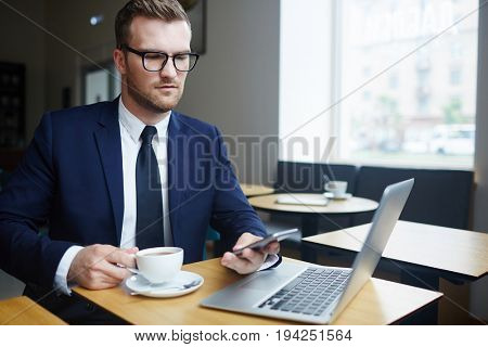 Professional trader having coffee in cafe and messaging