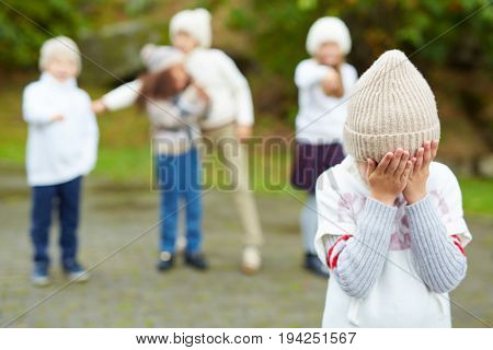 Portrait of little boy crying hiding his face with cruel kids pointing at him in background, bullying and calling him names