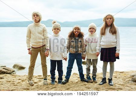 Group of cheerful children standing by lake in row, sticking out tongues while playing outdoors on warm autumn day all dressed in similar knit clothes