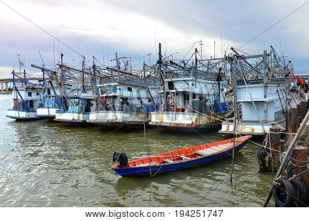 Fishery boats're mooring at the harbour for waiting to work next time photo in outdoor sun lighting.