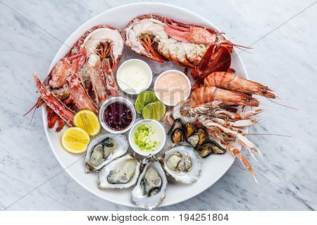 Fresh seafood platter with lobster, mussels and oysters on marble desk.