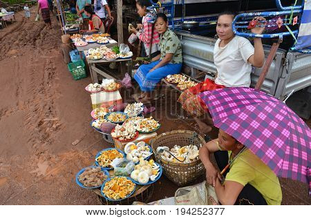 LOUNGPRABANG LAOS - AUGUST 4 : Unidentified woman monger sale mashroom and other things at the local road side market on August 4 2015 at Loungprabang city in Laos