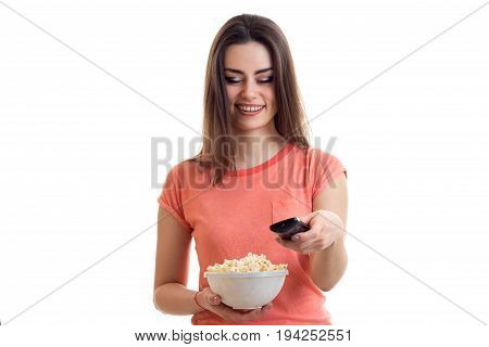 charming lady with pop corn in hand smiling and change channels remote control isolated on white background