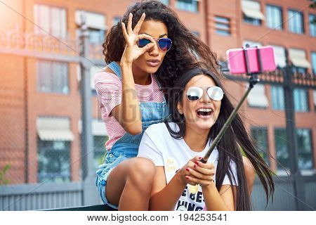 Two smiling young girlfriends sitting on a city bench making faces while taking self portraits together with a smartphone and selfie stick