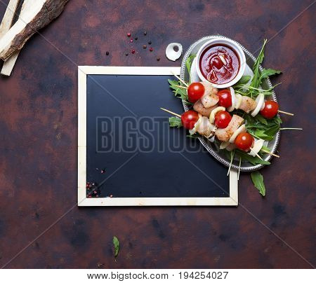 Raw shish kebabs on an iron plate with vegetables and greens near a coated board on a concrete background, flat lay copy space