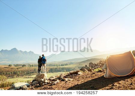 Rearview of a young couple standing on a rock looking at a mountain landscape while camping together in rugged terrain