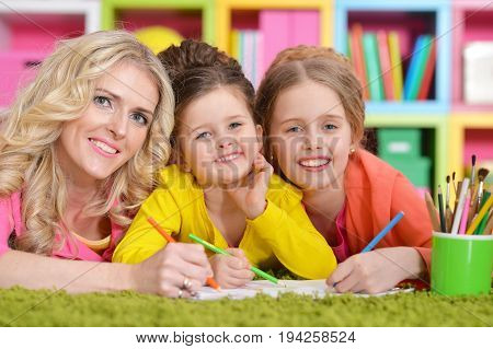 Mother with her daughters drawing in room with bookshelves