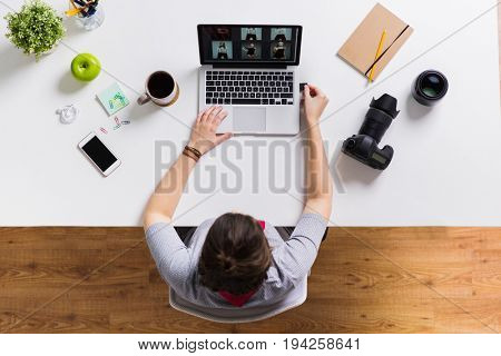 photography, people and technology concept - woman inserting camera flash drive into laptop computer at office table
