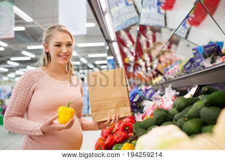 sale, shopping, food, pregnancy and people concept - happy pregnant woman with paper bag buying peppers at grocery store or supermarket