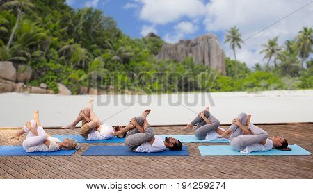 fitness, sport, yoga and healthy lifestyle concept - group of people making half ankle to knee supine pose over tropical beach background