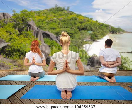 fitness, sport, yoga and healthy lifestyle concept - group of people exercising in reverse prayer pose over tropical beach background