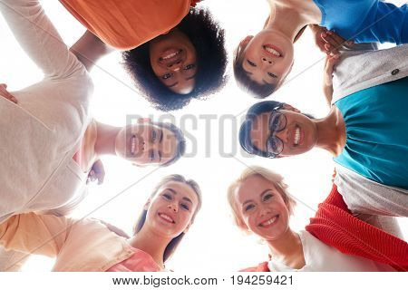 diversity, race, ethnicity and people concept - international group of happy smiling different women standing in circle and hugging over white