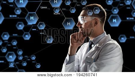 chemistry, science, and people concept - male doctor or scientist in white coat and safety glasses looking at virtual projection of chemical formula over black background