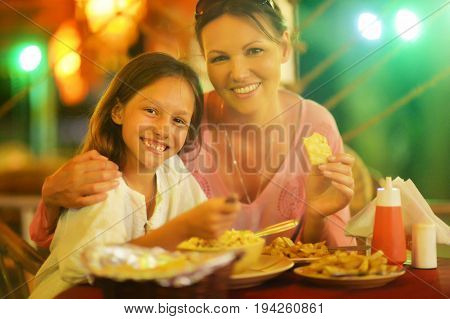Portrait of a mother and daughter eating in restaurant