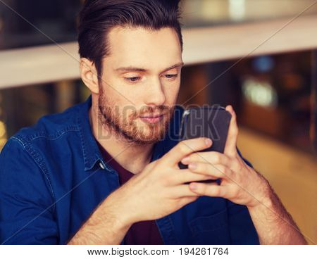 leisure, technology, internet addiction, lifestyle and people concept - man with smartphone reading message at restaurant