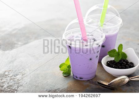 Berry bubble tea in plastic cups with lids and straws