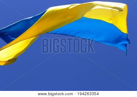 Flag of Ukraine waving in wind on clear blue sky at sun day
