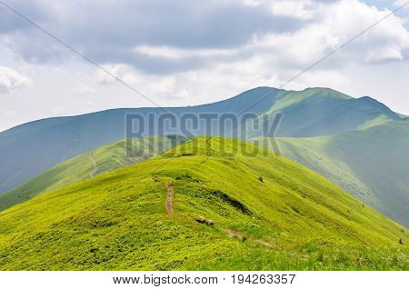 Mountains landscape. Green slopes and a path that runs along the top of the mountain. Nature backgrounds.