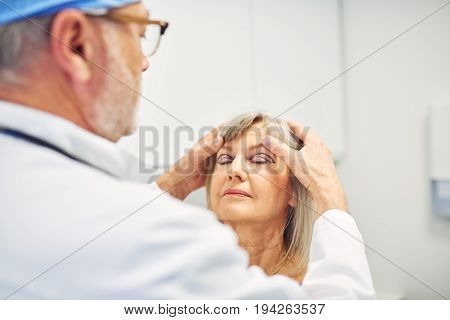 Cosmetics Surgeon Holding Adult Woman Head And Diagnosing