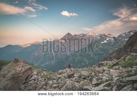 One Person Sitting On Rocky Terrain And Watching A Colorful Sunrise High Up In The Alps. Wide Angle