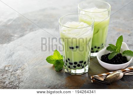 Matcha bubble tea with tapioca pearls in tall glasses