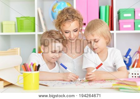 Portrait of happy mother drawing with three cute sons