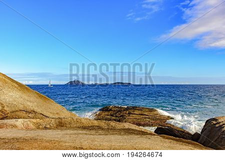 Sailboat sailing during the afternoon through the waters of Atlantic ocean in Rio de Janeiro