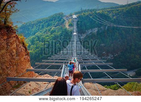 SOCHI, RUSSIA, SEP, 05, 2015: SKYPARK metal bridge stair staircase with tourists above river. SKYPARK MegaTroll bangee jumping adrenaline places for tourists. Best sightseeing holiday vacation tours