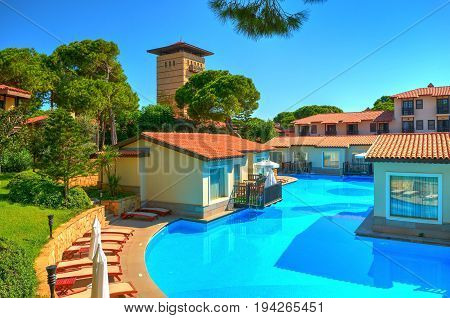 BELEK, TURKEY, SEP. 9, 2010: Summer view on luxury villas swimming pool in hotel Paloma Grida Village & Spa in Italian style. Italian architecture style. Turkey holidays vacations famous tours