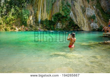 TURKEY, SEP. 10, 2010: Beautiful young girl in bikini is standing in green crystal clear water and shooting tropical water falls and stone rocks. Swimming tourists on sand beach. Romantic landscape
