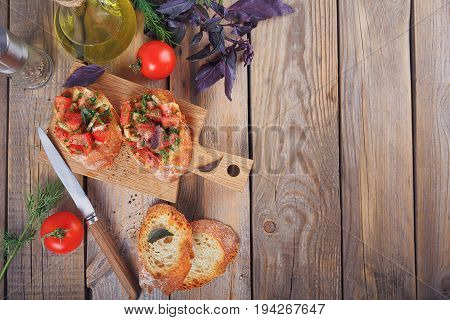 Italian bruschetta with chopped tomatoes basil herbs and olive oil on grilled crusty bread. Italian cuisine concept. Top view with space for text. Flat lay