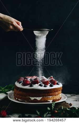 Woman sifting icing sugar over strawberry sponge cake