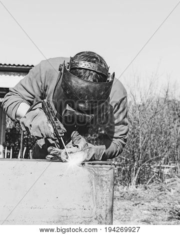 Welder puts a seam on metal electro arc welding black and white toning photo