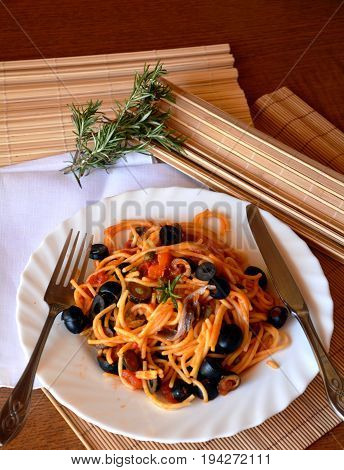 Delicious italian pasta spaghetti with anchovies on a bowl on a table.