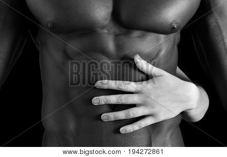 A white woman's hand on a muscular belly of a black man