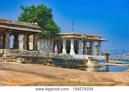 Hampi, India - November 19, 2012: Indian woman in traditional clothes stands at the ancient ruins of Hemakuta hill in Hampi, Karnataka, India. UNESCO World Heritage Site