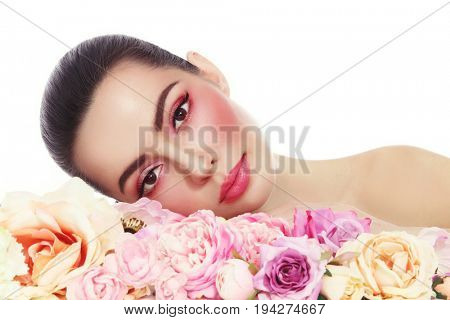Young beautiful woman with fresh make-up and flowers over white background, copy space