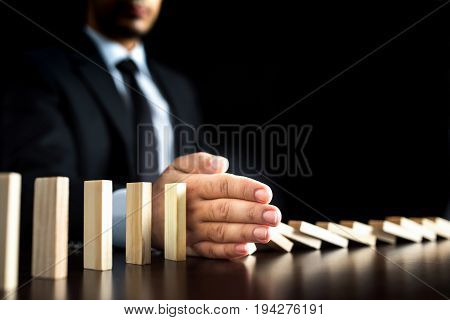 Chain Reaction In Business Concept Businessman Letting Or Preventing Dominoes Continuous Toppling On Rustic Wooden Desk