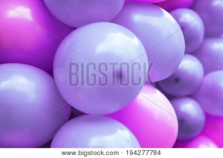 A background of pink and purple balloons.